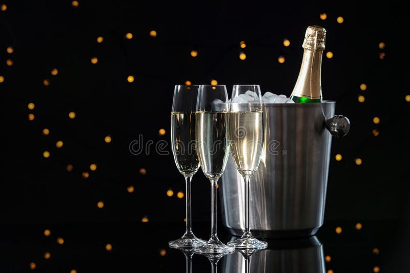 Glasses with champagne and bottle in bucket. On dark table against blurred lights royalty free stock image