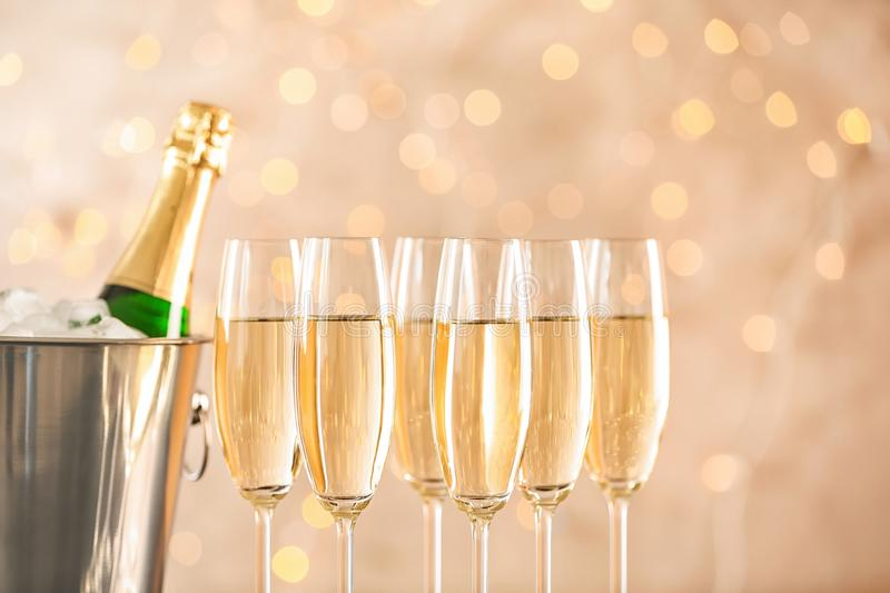 Glasses with champagne and bottle in bucket. Against blurred lights stock photo