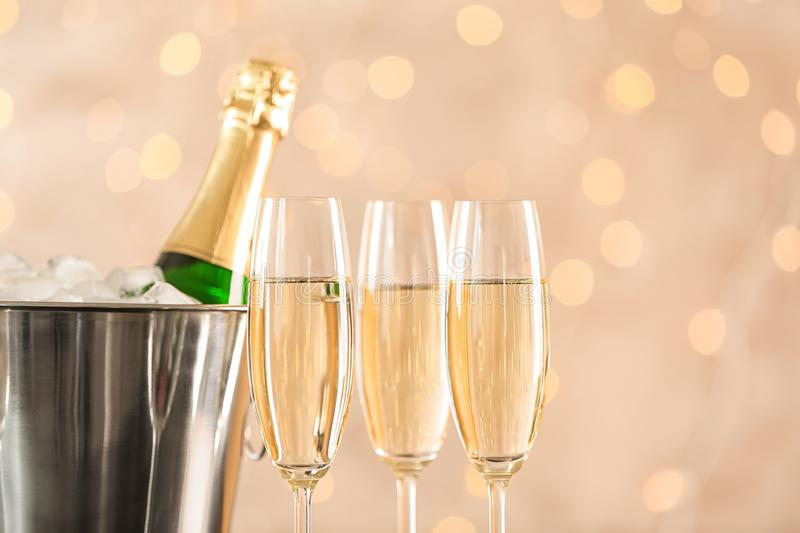 Glasses with champagne and bottle in bucket. Against blurred lights royalty free stock image