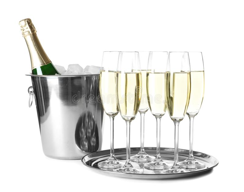 Glasses with champagne and bottle in bucket. On white background royalty free stock photo