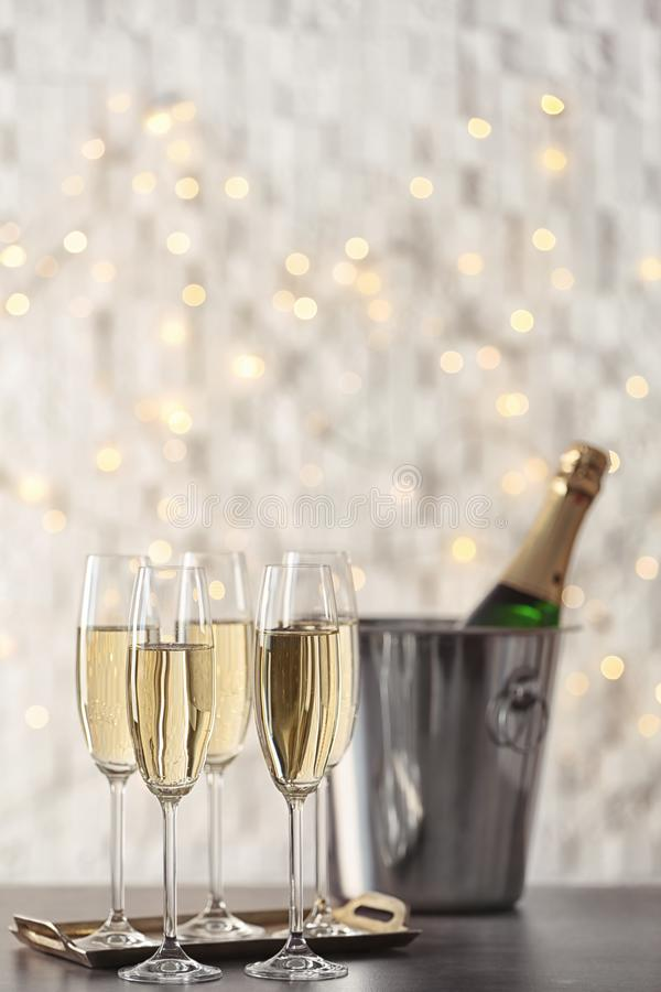 Glasses with champagne and bottle in bucket. On table against blurred lights royalty free stock photo
