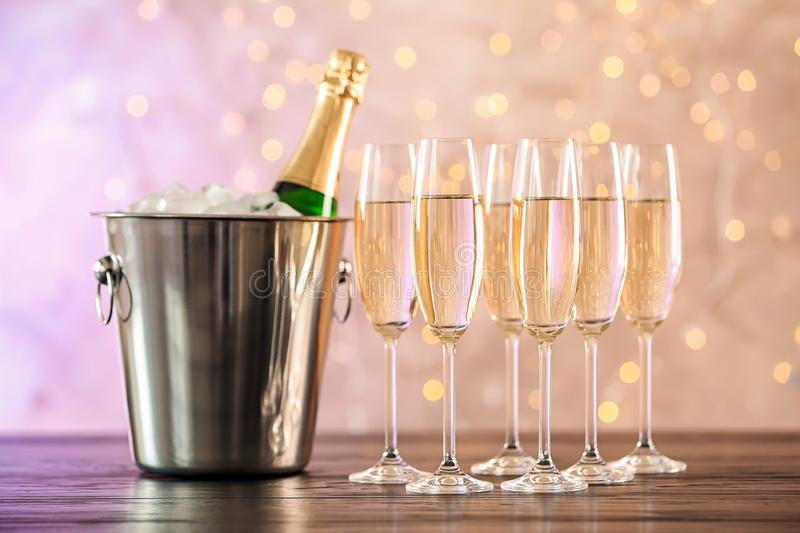 Glasses with champagne and bottle in bucket. On table against blurred lights royalty free stock photos