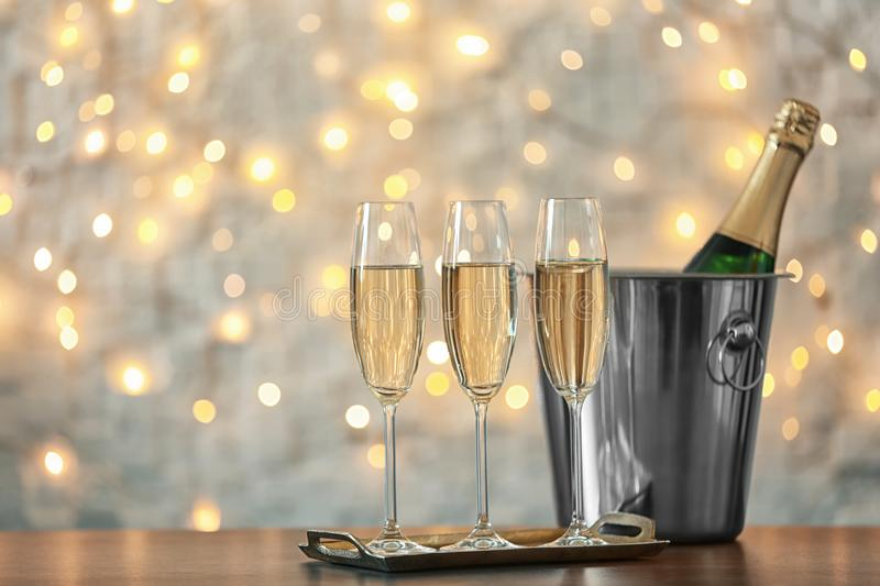 Glasses with champagne and bottle in bucket. On table against blurred lights royalty free stock photography