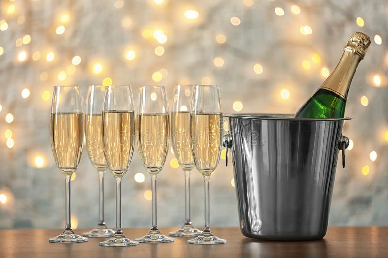 Glasses with champagne and bottle in bucket on table stock image