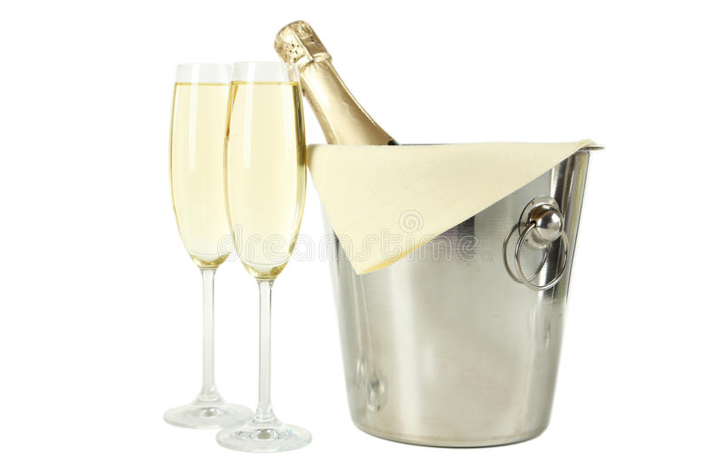 Glasses of champagne with bottle in a bucket on white stock images