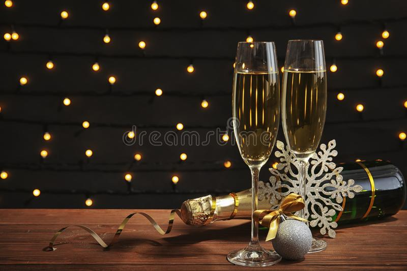 Glasses of champagne with bottle and festive deco. R on table against blurred fairy lights royalty free stock images