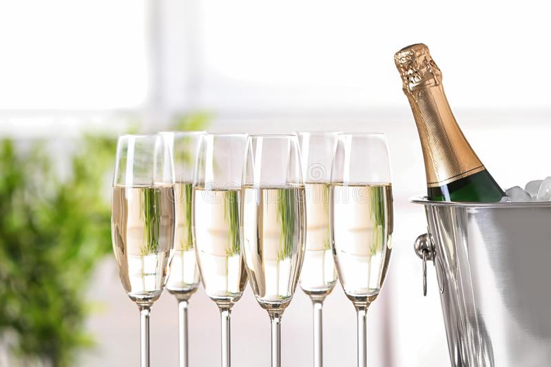 Glasses with champagne and bottle. In bucket against blurred background royalty free stock photos
