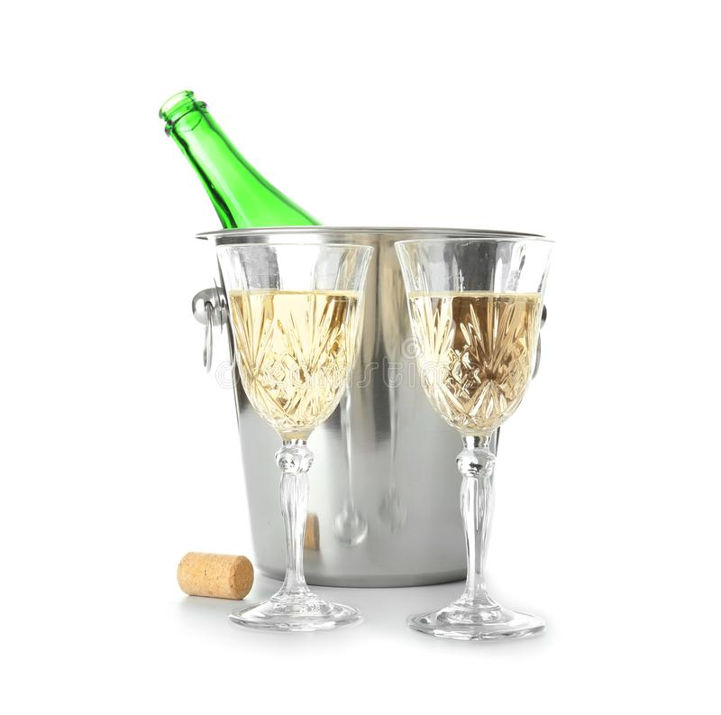 Glasses of champagne and bottle in ice bucket on white background royalty free stock photo