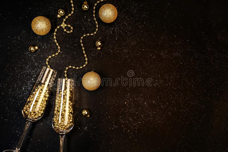 Glasses with champagne gold decor on a black background. Christmas, New Year celebration Flat lay celebration concept royalty free stock image