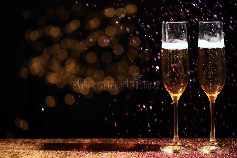 Glasses of champagne and golden glitter on table against blurred background. royalty free stock images