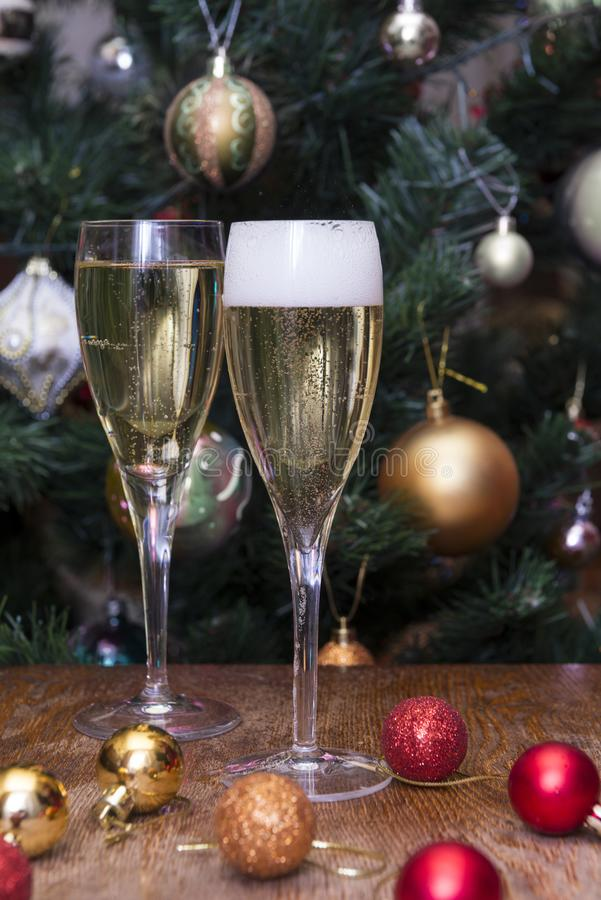 2 glasses of champagne, Golden and red Christmas balls on the background of decorated Christmas tree, drink, alcohol royalty free stock photography