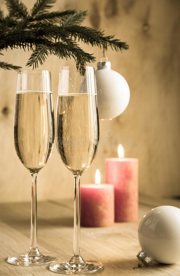 Glasses of champagne under decorated christmas tree branch stock photo