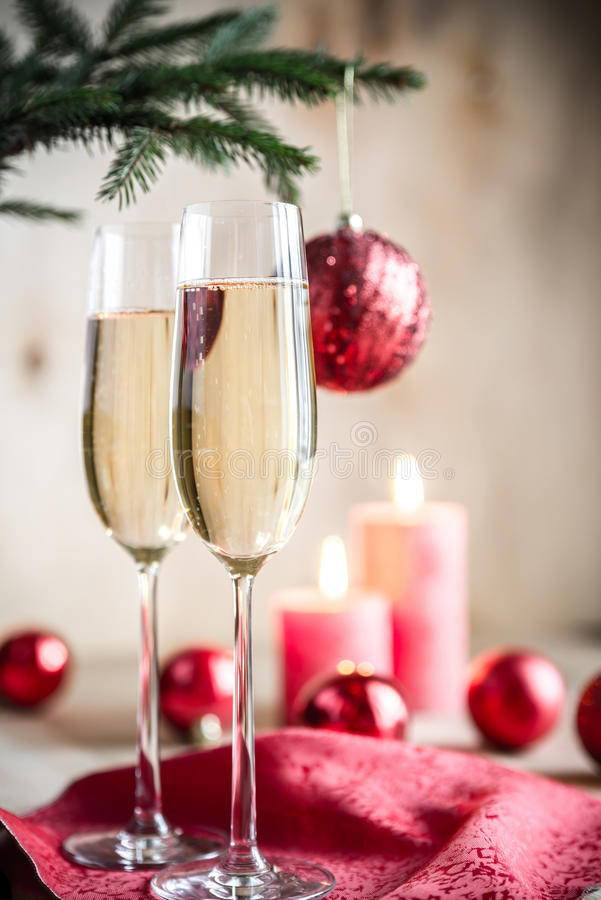 Glasses of champagne under decorated christmas tree branch stock images