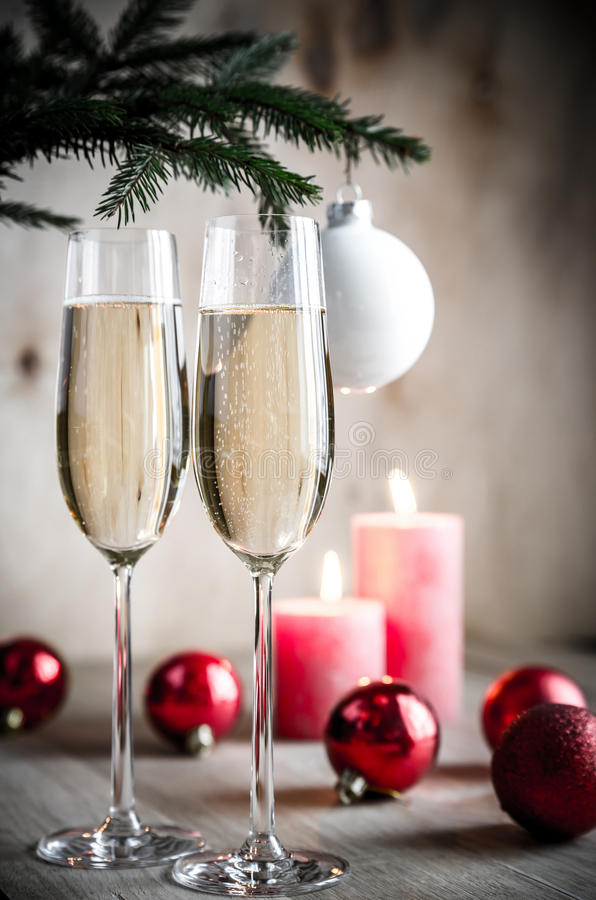 Glasses of champagne under decorated christmas tree branch royalty free stock photo