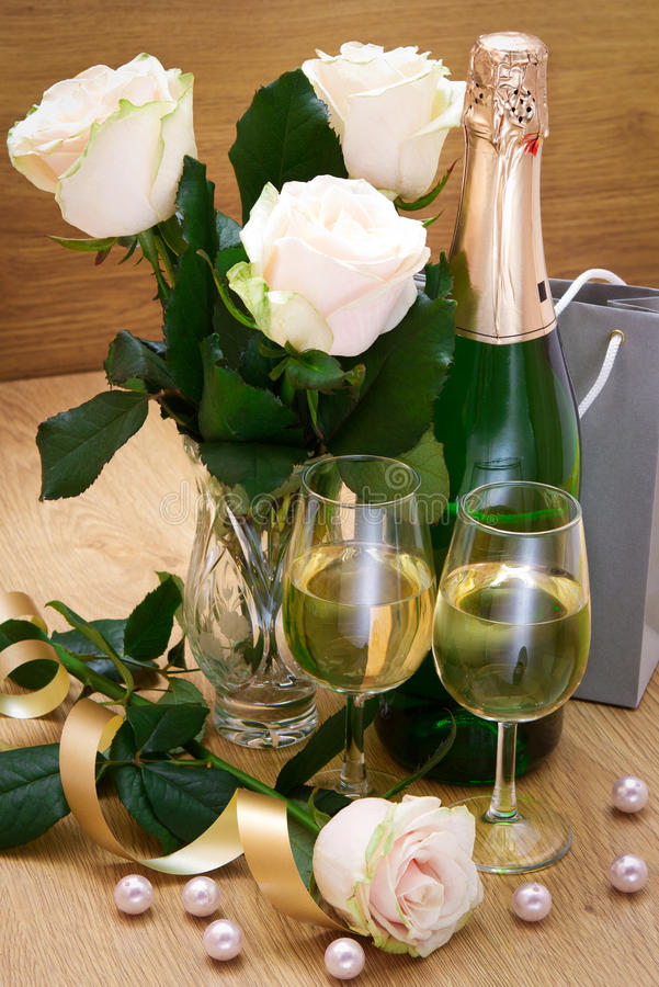 Glasses with champagne and white roses stock image