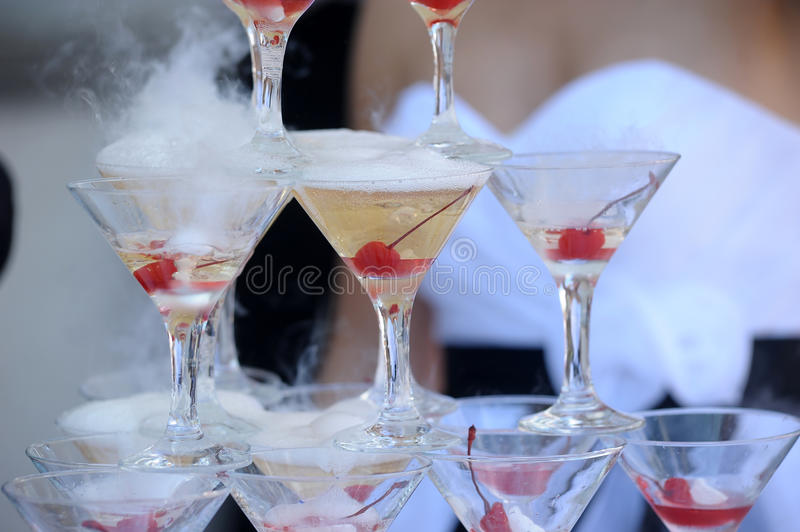 Glasses with cherry and smoke. Champagne glasses tower in celebration party stock image