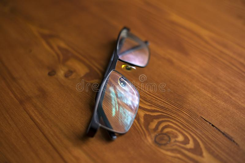 Glasses with transparent lenses to improve vision on a wooden background close-up royalty free stock images