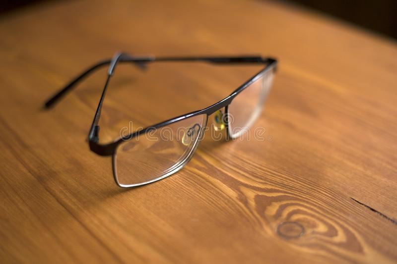 Glasses with transparent lenses to improve vision on a wooden background close-up stock photos