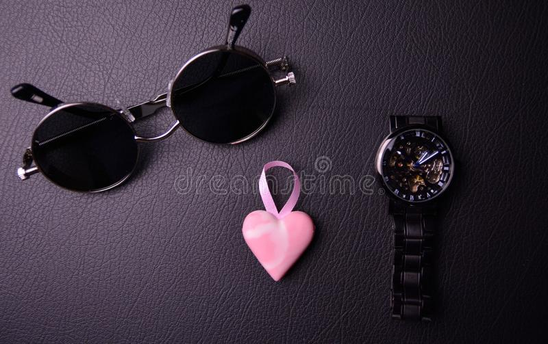 glasses and clock in the style of steampunk with a pink heart in the center on a black background stock photography