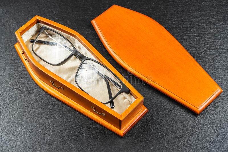 Glasses in coffin.Laser eye surgery or Buy Your Contact Lenses concept royalty free stock photography