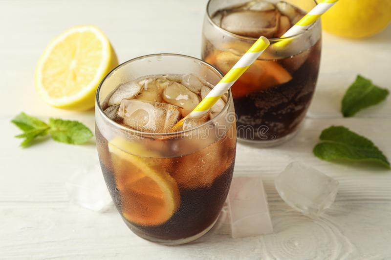 Glasses with cold cola and citrus on white cement background. Closeup stock photo