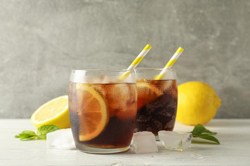 Glasses with cold cola and citrus on white cement background. Space for text royalty free stock photo