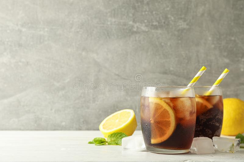 Glasses with cold cola and citrus on white cement background. Space for text royalty free stock photos