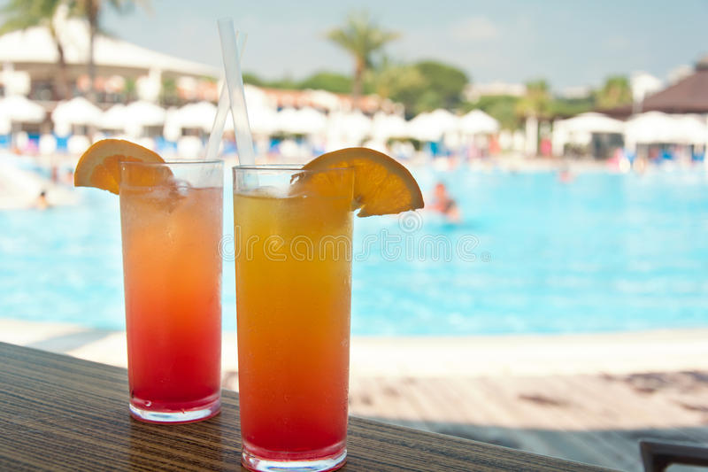 Glasses with colored cocktails on the side of a swimming pool stock image