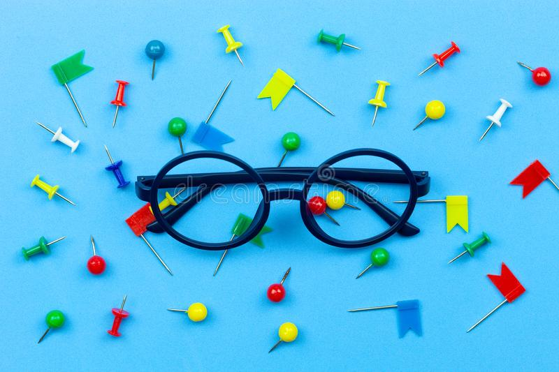 Glasses with colorful push pin on blue paper background. stock photo