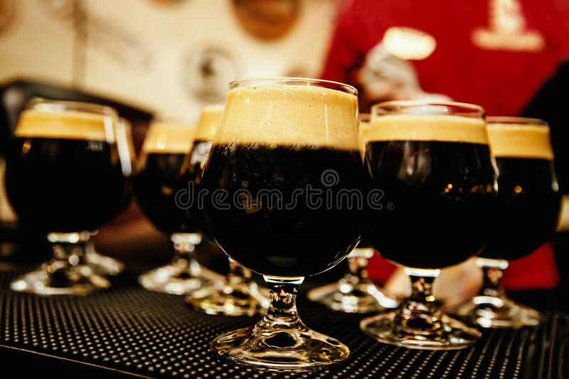 Glasses of dark beer with froth stock photos
