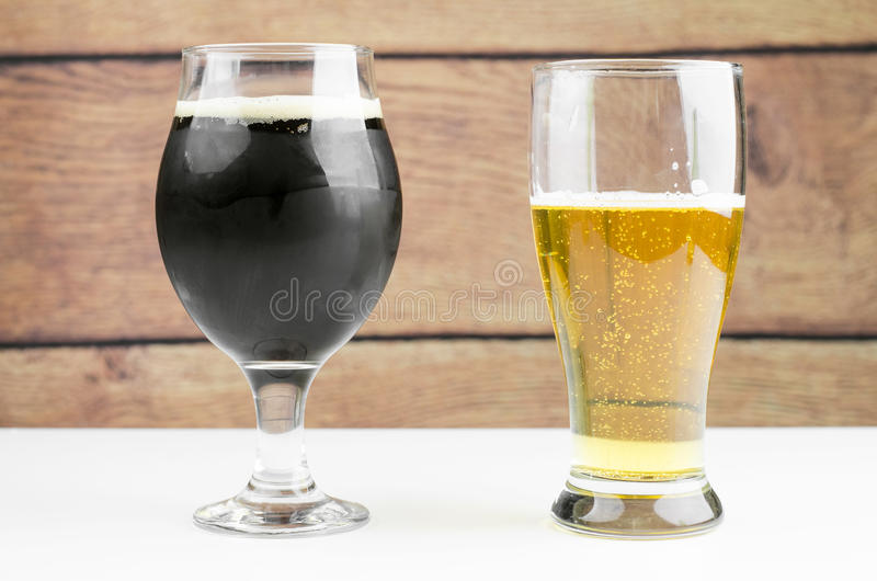 Glasses Of Dark And Light Beers. On White Table And Wooden Background stock photography