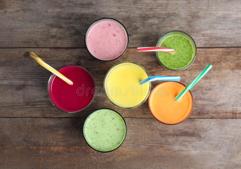 Glasses with delicious detox smoothies. On wooden background, top view stock photos
