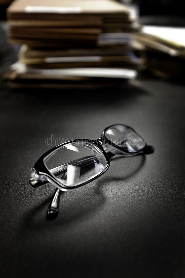 Glasses on Desk With Files Business Education Folders Papers. Glasses on desk with files and folders for business education work royalty free stock photography