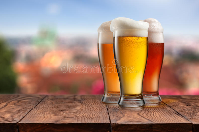 Glasses of different beer on wooden table against Prague royalty free stock photography