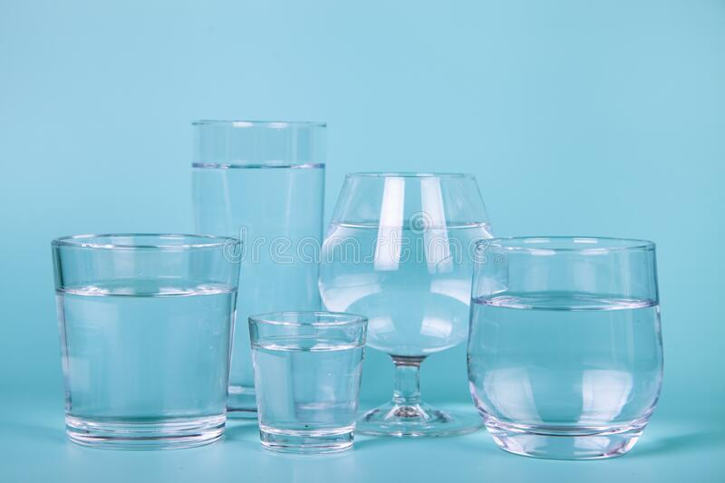 Glasses of different shapes with water stock image