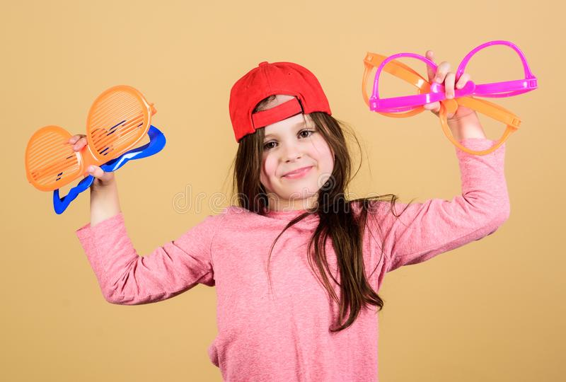 Glasses do more than improve your vision. Cute small kid holding party glasses. Cool party girl choosing fancy glasses. Stylish little child with fashion stock photos