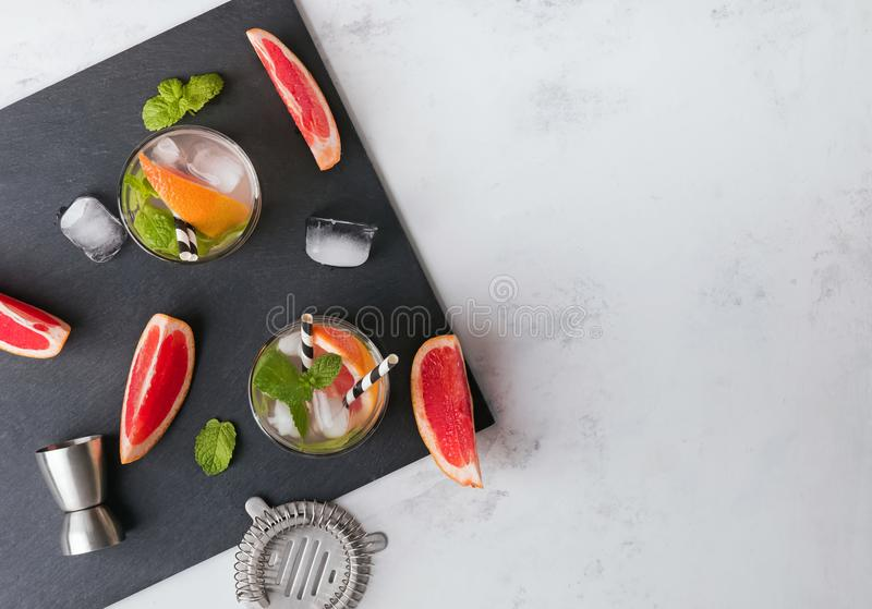 Glasses with drink, bar equipment and pieces of grapefruit on the black slate stone, top view. Making grapefruit cocktail. Glasses with drink, bar equipment and royalty free stock photo