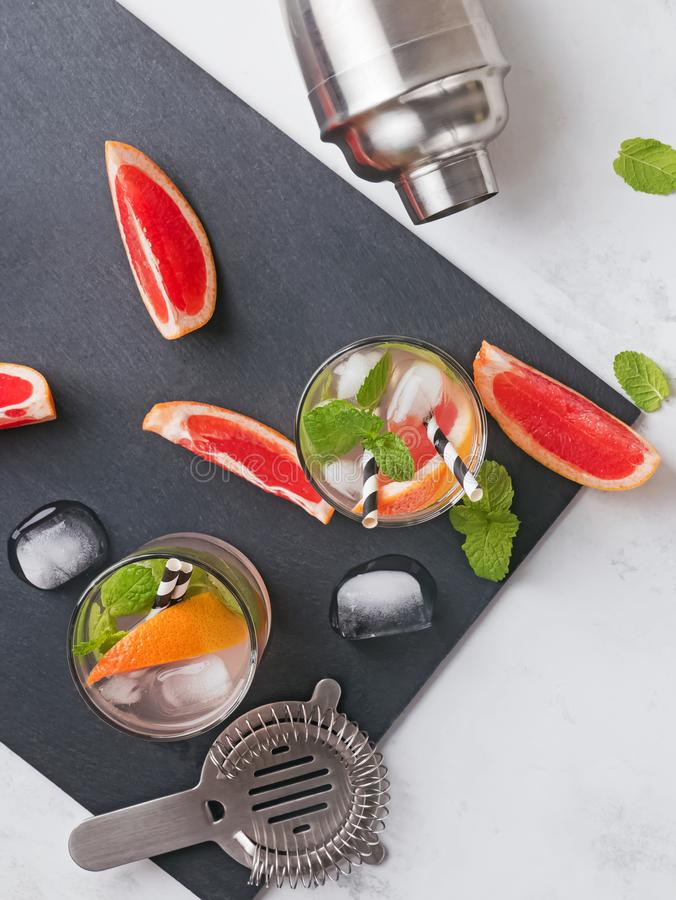 Glasses with drink, bar equipment and pieces of grapefruit on the black slate stone, top view. Making grapefruit cocktail. Glasses with drink, bar equipment and stock photo