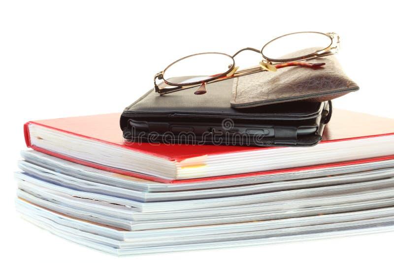 Glasses eBook reader pile of books stock photo