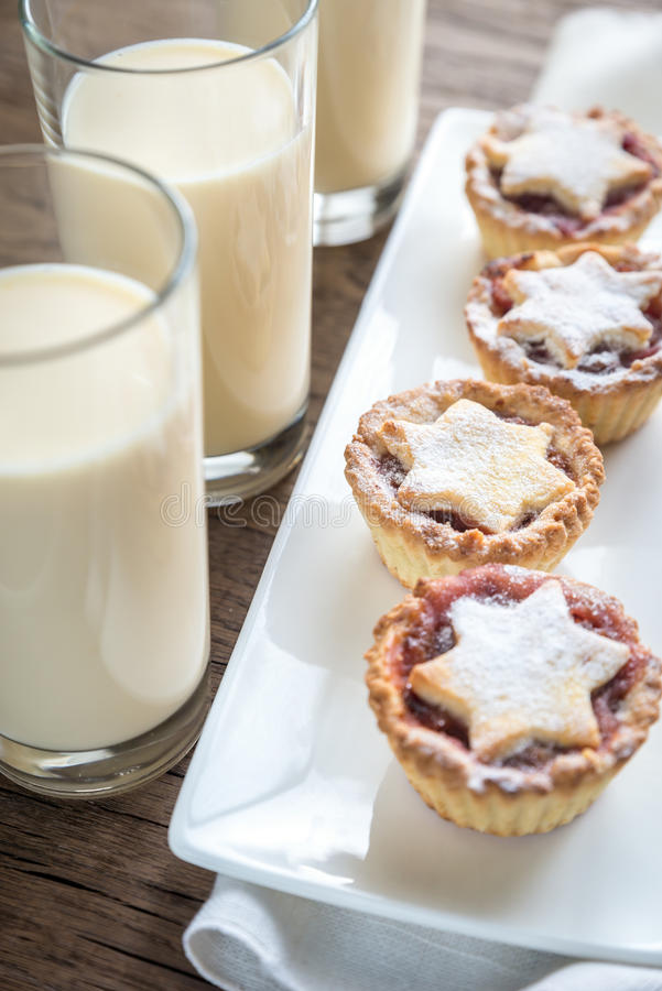 Glasses of eggnog with mince pies royalty free stock images