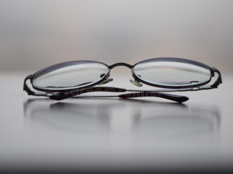 Glasses eyewear on the white desk. Closeup clear glasses eyewear Black frame on the white desk royalty free stock images