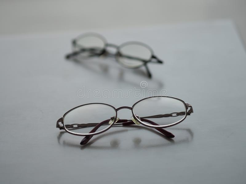 Glasses eyewear on the white desk. Closeup clear glasses eyewear Black frame on the white desk royalty free stock image