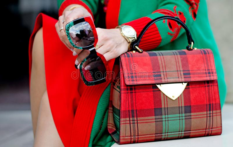 Glasses in female hands. Bag close up. Scottish plaid bag. Stylish modern and feminine image, style. Women`s accessories: watches, stock photography