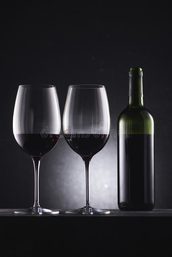 Glasses filled with red wine and wine bottle. On black royalty free stock photos