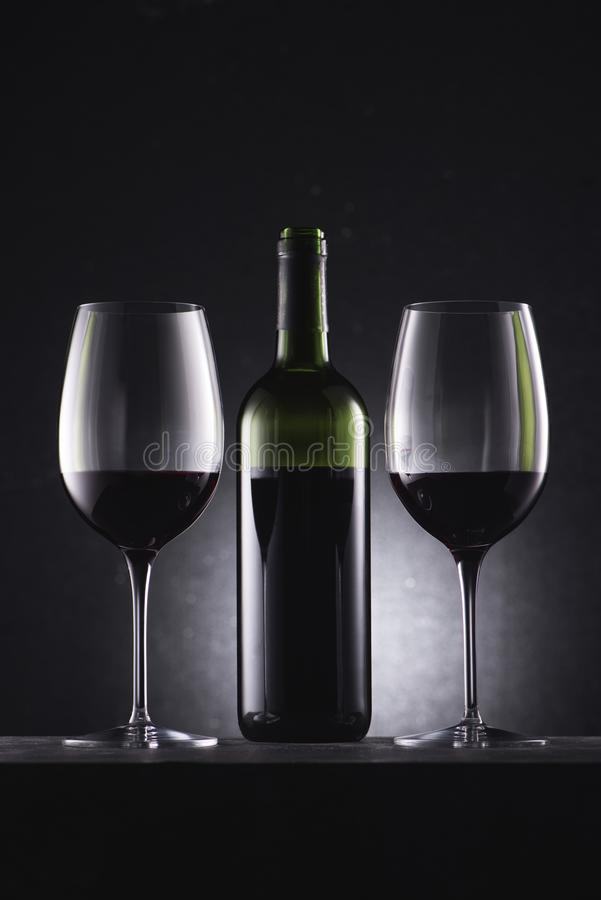 Glasses filled with red wine and wine bottle in middle. On black stock photography