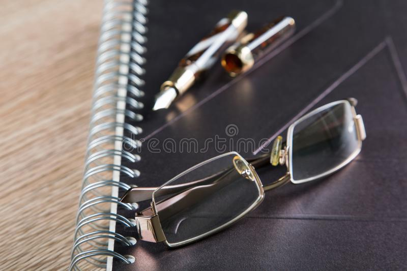 Glasses fountain pens and diaries stock images