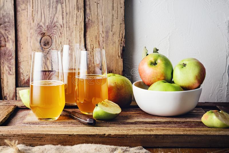 Glasses of fresh apple juice. And apples on a wooden table stock photos