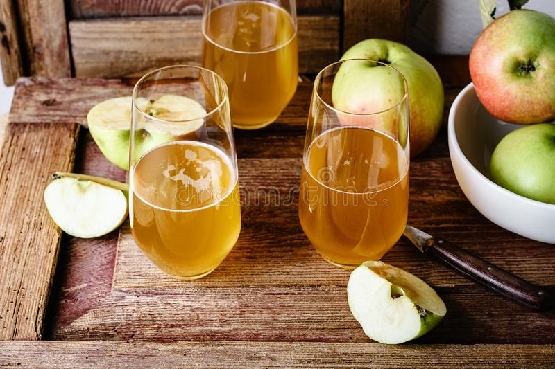 Glasses of fresh apple juice. And apples on a wooden table stock photo