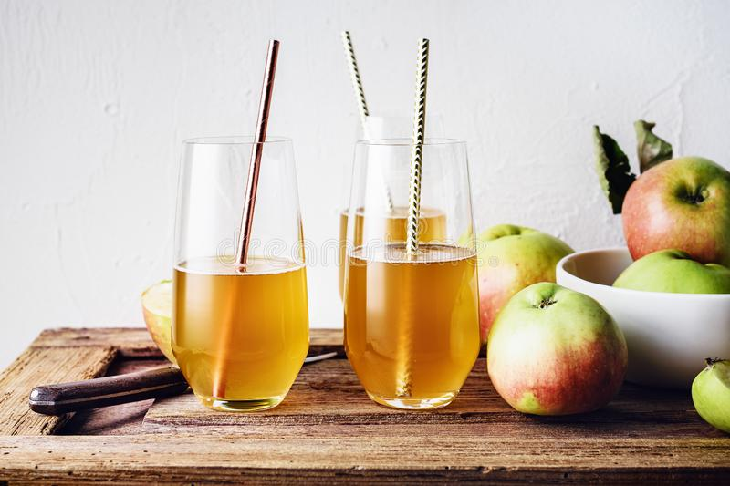 Glasses of fresh apple juice. And apples on a wooden table royalty free stock photo