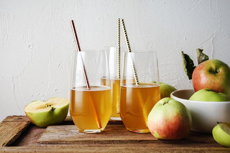 Glasses of fresh apple juice. And apples on a wooden table royalty free stock photography